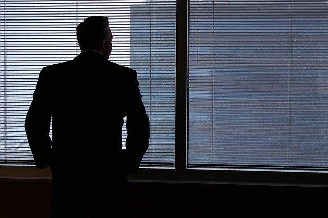 mężczyzna stojący przed oknie w biurze